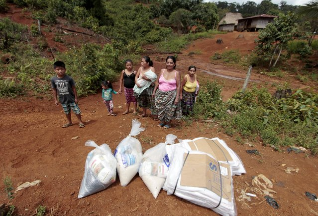 Women and children stand next to food supplies for victims of heavy rains in the village of Cotoxa, in the Izabal region, near Guatemala City, August 8, 2015. (Photo by Josue Decavele/Reuters)