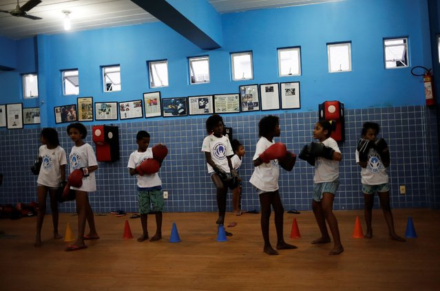 Children talk during an exercise session at a boxing school, in the Mare favela of Rio de Janeiro. (Photo by Nacho Doce/Reuters)