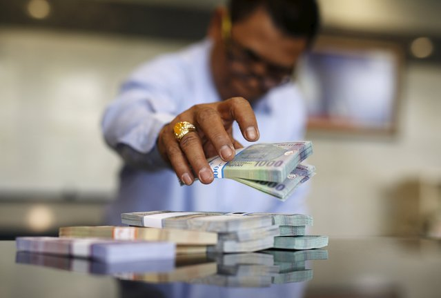 A teller at Bank Indonesia counts out Rupiah bank notes at their headquarters in Jakarta in this October 27, 2014 file photo. (Photo by Darren Whiteside/Reuters)