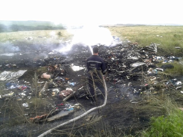 A man works at putting out a fire at the site of a Malaysia Airlines Boeing 777 plane crash in the settlement of Grabovo in the Donetsk region, July 17, 2014. The Malaysian airliner was shot down over eastern Ukraine by pro-Russian militants on Thursday, killing all 295 people aboard, a Ukrainian interior ministry official said. (Photo by Maxim Zmeyev/Reuters)