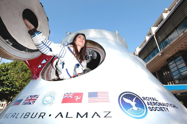 Jenn Sander from Red Robin PR, wearing a spacesuit once worn by US Astronaut Peggy Whitson, sits inside a re-entry capsule owned by Excalibur Almaz