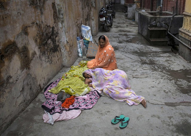 Devki Rai, 49, lies next to the body of her mother Champa Devi, minutes after her death at the Mukti Bhavan (Salvation House) in Varanasi, in the northern Indian state of Uttar Pradesh, June 21, 2014. (Photo by Danish Siddiqui/Reuters)
