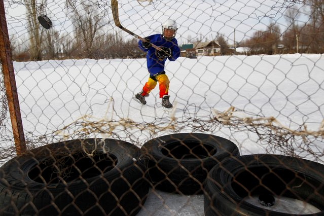 A young hockey player practices his putting during a training session in the village of Otradnoye, Kyrgyzstan on February 4, 2020. (Photo by Vladimir Pirogov/Reuters)