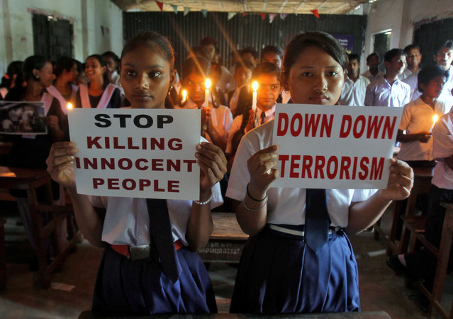 School children hold candles and placards as they pray during a vigil to show solidarity with the victims of the attack at Turkey's largest airport, Istanbul Ataturk, in Agartala, India, June 29, 2016. (Photo by Jayanta Dey/Reuters)