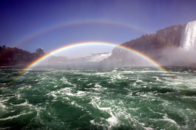 Niagara Falls are seen with a double rainbow 8 October 2006 from aboard the Maid of the Mist on the Niagara River. Under the rainbow the American Falls can be seen. (Photo by Don Emmert/AFP Photo)