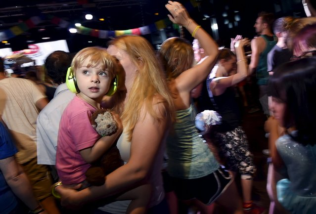 """A woman holds her child as club-goers dance at """"Morning Gloryville"""" at the Ministry of Sound in south London August 11, 2015. (Photo by Toby Melville/Reuters)"""