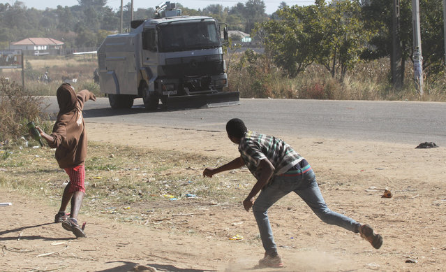 Rioters battle with Zimbabwean police in Harare, Monday, July, 4, 2016. Police in Zimbabwe's capital fired tear gas and water cannons in an attempt to quell rioting by taxi and mini bus drivers protesting what they describe as police harassment.  The violence came amid a surge in protests in recent weeks because of economic hardships and alleged mismanagement by the government of President Robert Mugabe. (Photo by Tsvangirayi Mukwazhi/AP Photo)