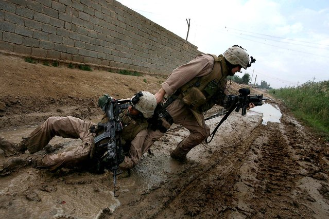 Sgt. Jesse E. Leach, squad leader of 4th Mobile Assault Platoon, 2nd Battalion, 1st Marines, pulls LCpl. Valdez-Castillo, wounded by a sniper, towards a safer area on October 31, 2006 in Karma, Iraq. Valdez-Castillo survived