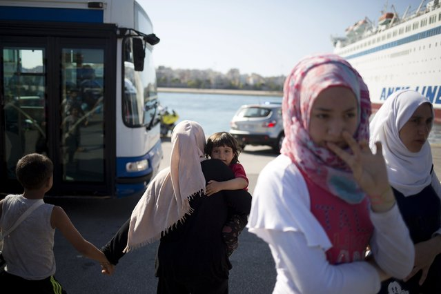 """A Syrian refugee woman carries a child as they try to catch a bus following their arrival onboard """"Eleftherios Venizelos"""" passenger ship at the port of Piraeus near Athens, Greece, August 20, 2015. (Photo by Stoyan Nenov/Reuters)"""