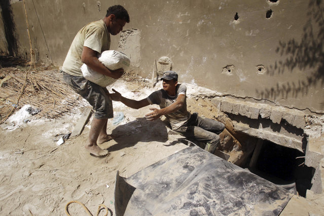 Palestinians smuggle cement outside a tunnel beneath the Egyptian-Gaza border in Rafah, in the southern Gaza Strip September 17, 2012. (Photo by Ibraheem Abu Mustafa/Reuters)