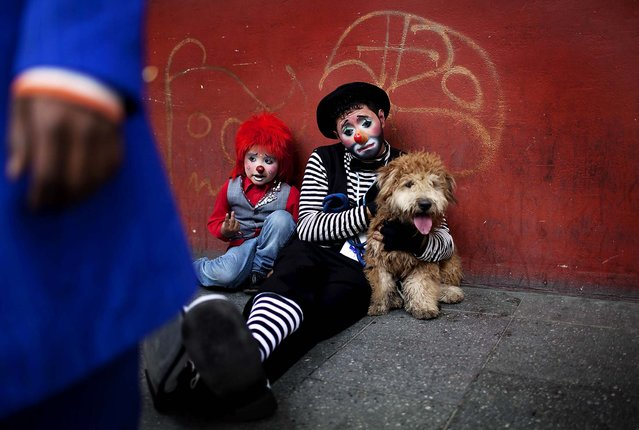 Two clowns take a rest on a sidewalk during the fourth annual Latin American Clown Congress in Guatemala City on July 24, 2012. Clowns from Central America and South America and the Caribbean have gathered for three days to exchange ideas and attend workshops. (Photo by Rodrigo Abd/Associated Press)
