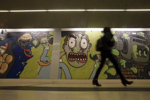 A woman walks past murals adorning the walls of Garibaldi subway station, in Milan, Friday, February 28, 2020. Due to the COVID-19 virus outbreak in northern Italy, the bustling metropolis of Milan has resembled more of a ghost town lately, as workers stayed home and tourism has dwindled there, and other parts of Italy. (Photo by Luca Bruno/AP Photo)