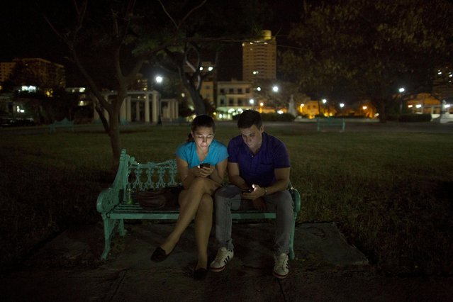 English teacher and social communications student Claudia Mas, 24, (L), and her brother Humberto Gomez, a journalism student, 24, listen to music with their cell phones in a park in Havana, March 14, 2015. (Photo by Alexandre Meneghini/Reuters)