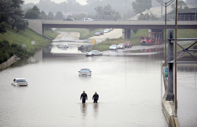 Cars are stranded along a flooded stretch of Interstate 696 at the Warren, Mich., city limits Tuesday morning, August 12, 2014. Police divers are searching for anyone trapped in their vehicles. Warren Mayor James Fouts said roughly 1,000 vehicles had been abandoned in floodwaters in the suburb where many roads were closed after 5.2 inches of rain fell Monday. (Photo by David Coates/AP Photo/Detroit News)