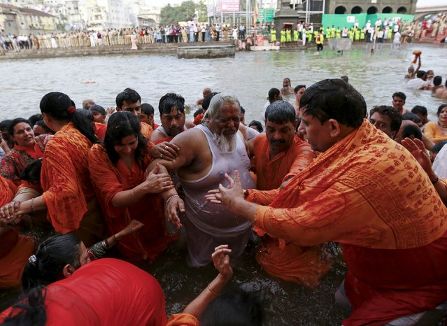 A Sadhu or Hindu holy man is helped by devotees after taking a dip in the Godavari river during the first Shahi Snan (grand bath) at Kumbh Mela, or Pitcher Festival in Nashik, India, August 29, 2015. (Photo by Danish Siddiqui/Reuters)