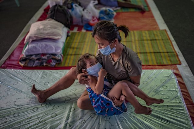 A homeless child and her mother wearing facemasks rest inside a gymnasium converted into a shelter for the homeless who are unable to feed themselves and unable to work because of government lockdown measures on April 1, 2020 in Manila, Philippines. The Philippine government has sealed off Luzon, the country's largest and most populous island, to prevent the spread of COVID-19. Land, sea, and air travel has been suspended, while government work, schools, businesses, and public transportation have been ordered shut in a bid to keep some 55 million people at home. The Philippines' Department of Health has so far confirmed 2,311 cases of the new coronavirus in the country, with at least 96 recorded fatalities. (Photo by Ezra Acayan/Getty Images)