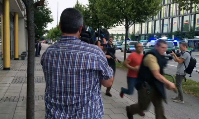 Armed police move past onlooking media responding to a shooting at a shopping center in Munich, Germany, Friday July 22, 2016. Munich police confirm shots have been fired at Olympia Einkaufszentrum shopping center but say they don't have any details about casualties. Police are responding in large numbers. (Photo by AP Photo/APTV)