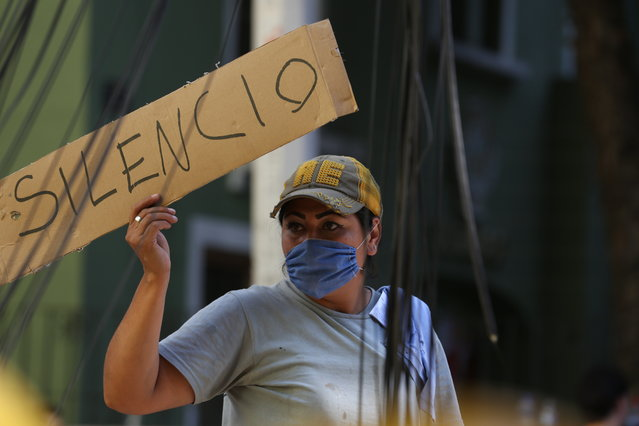 """A woman holds a sign the reads in Spanish """"Silence"""" as first responders work on removing the rubble of a collapsed building looking for survivors trapped underneath, after a 7.1 earthquake in Mexico City, Tuesday, September 19, 2017. (Photo by Gustavo Martinez Contreras/AP Photo)"""