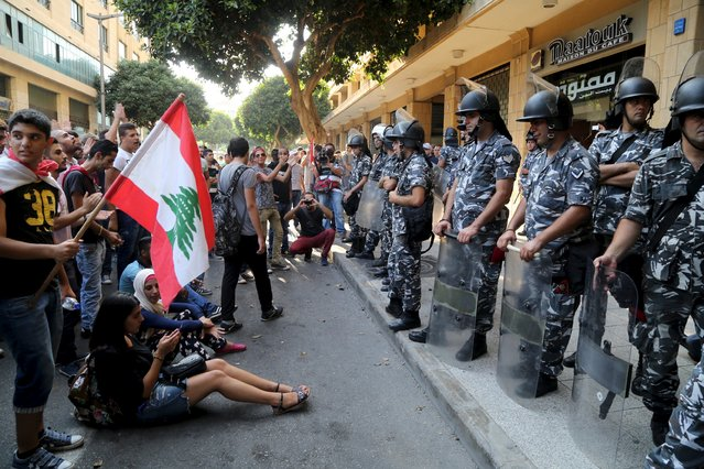 Protestors carry a Lebanese flag in front of riot police at one of the entrances to the environment ministry in downtown Beirut, Lebanon September 1, 2015. Dozens of protesters occupied the environment ministry in the Lebanese capital Beirut on Tuesday calling on minister Mohamad Al Machnouk to resign over a rubbish disposal crisis, the latest in a wave of protests against the paralysed political system. (Photo by Aziz Taher/Reuters)