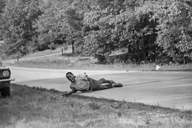 In this  June 6, 1966 file photo, civil rights activist James Meredith pulls himself across Highway 51 after being shot in Hernando, Miss. Meredith, who defied segregation to enroll at the University of Mississippi in 1962, completed the march from Memphis, Tenn., to Jackson, Miss., after being treated for his wounds. (Photo by Jack Thornell/AP Photo)