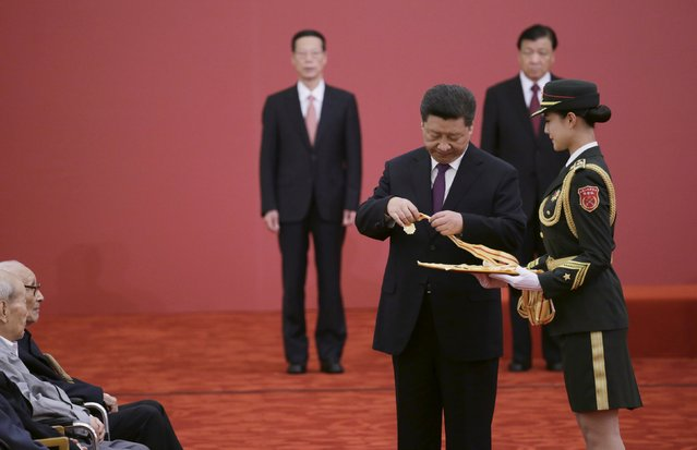 China's President Xi Jinping holds a commemorative medal before presenting to veterans at a medal ceremony marking the 70th anniversary of the Victory of Chinese People's War of Resistance Against Japanese Aggression, for World War Two veterans, at the Great Hall of the People in Beijing, China September 2, 2015. (Photo by Jason Lee/Reuters)