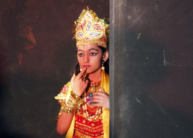 A girl dressed as Krishna waits backstage to perform during celebrations ahead of the Janmashtami festival in Ahmedabad August 25, 2013. (Photo by Amit Dave/Reuters)