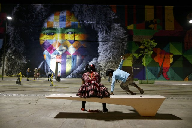 Locals sit in front of a mural created by Brazilian artist Eduardo Kobra that covers nearly 3,000 square meters of wall space Rio de Janeiro, Brazil on July 30, 2016. (Photo by Ivan Alvarado/Reuters)
