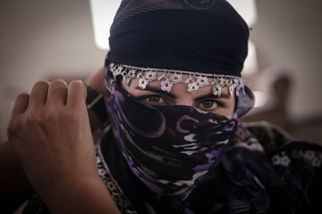 YPJ soldier Narlene, 20, puts a scarf around her face at an abandoned Iraqi Army Post on the outskirts of Raabia, Syria, August 9, 2014. On the desolate Syrian-Kurdistan border live many YPG / YPJ soldiers, who are staked out at  makeshift posts to fend of IS attacks and protect the border. (Photo by Erin Trieb/NBC News)