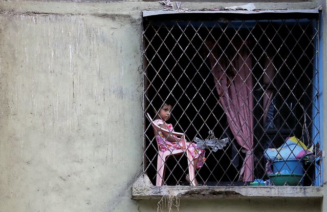 A girl watches as the Sri Lankan Army musical band performs to entertain the people who are stuck inside their houses, during a curfew imposed by the government amid concerns about the spread of coronavirus disease (COVID-19), in Colombo, Sri Lanka, April 6, 2020. (Photo by Dinuka Liyanawatte/Reuters)