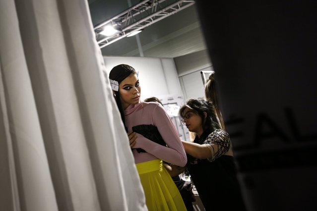 A model wears a creation by Portuguese designer Dino Alves as she is prepared backstage during the Lisbon Fashion Week, at the Carlos Lopes Pavillion, in Lisbon, Portugal, 07 October 2017 (issued 08 October 2017). (Photo by Rodrigo Antunes/EPA/EFE)