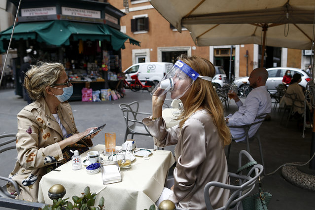 A woman sips her coffee from under her facial protection at a cafe with outdoor tables in Rome Monday, May 18, 2020. Italy is slowly lifting restrictions after a two-month coronavirus lockdown. (Photo by Cecilia Fabiano/LaPresse via AP Photo)