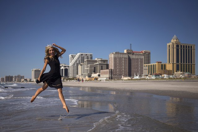 """Newly-crowned Miss America 2015 Kira Kazantsev leaps into the air while posing for photographs during her """"Toe Dip"""" along the beachfront of Boardwalk Hall the morning after she won the 2015 Miss America Competition in Atlantic City, New Jersey September 15, 2014. (Photo by Adrees Latif/Reuters)"""