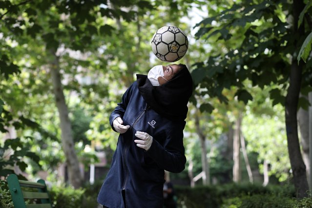 Iranian freestyle footballer Hosna Mirhadi, 23, wears a protective face mask and gloves as she trains with a ball, following the outbreak of the coronavirus disease (COVID-19), at a park in Tehran, Iran, May 5, 2020. (Photo by WANA (West Asia News Agency) via Reuters)
