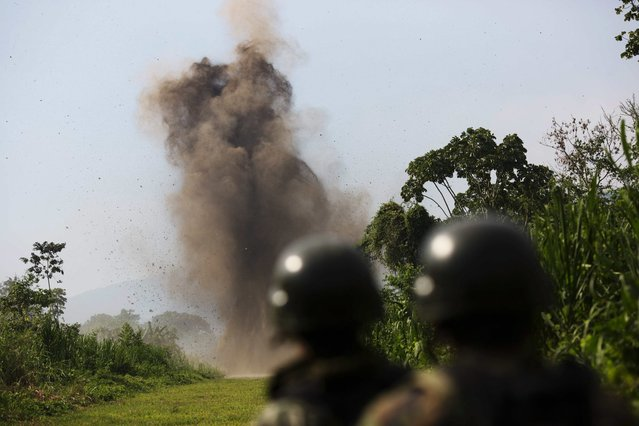 In this September 19 2014 photo, Peruvian counternarcotics forces watch the detonantion of explosives they planted on a part of a clandestine grassy airstrip in the Valley of the Apurimac, Ene and Mantaro River Valleys, or VRAEM, the world's No. 1 coca-growing region in Ayacucho, Peru. Peruvian authorities have launched an operation to destroy clandestine airstrips used by drug traffickers. (Photo by Rodrigo Abd/AP Photo)