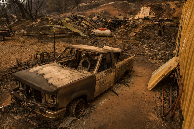Burnt remains of a vehicle left behind remains off Jesus Maria Road near Mokelumne Hill, Calif., Friday, September 11, 2015. The wildfire in Northern California that exploded in size has destroyed multiple homes in Amador County as evacuations remained in place Thursday, Cal Fire officials said. (Photo by Andrew Seng/The Sacramento Bee via AP Photo)