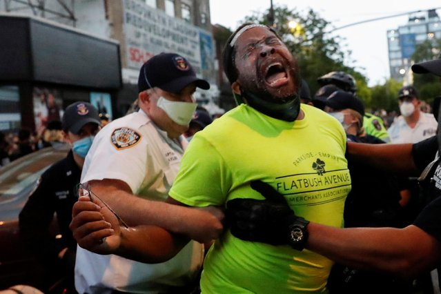 """Police officers detain a man during an """"I can't breathe"""" vigil and rally in the Brooklyn borough of New York, NY, U.S., following the death of African-American George Floyd who was seen in graphic video footage gasping for breath as a white officer knelt on his neck in Minneapolis, Minnesota, May 29, 2020. (Photo by Shannon Stapleton/Reuters)"""