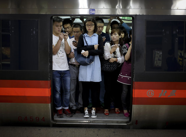 Commuters with their smartphones crowd inside a subway train during a rush hour in Beijing, China Monday, September 22, 2014. Asian shares were mostly lower Monday as investors awaited the release of a preliminary manufacturing survey from China this week that might show renewed weakness in the world's second-largest economy. (Photo by Andy Wong/AP Photo)