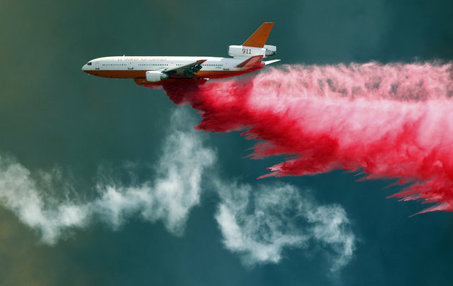 A DC-10 air tanker delivers flame retardant to the Blue Cut fire in Wrightwood, Calif., Wednesday, August 17, 2016. A wildfire with a ferocity never seen before by veteran California firefighters raced up and down canyon hillsides, instantly engulfing homes and forcing thousands of people to flee, some running for their lives just ahead of the flames. (Photo by Alex Gallardo/AP Photo)