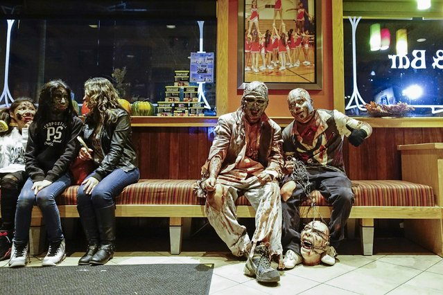 Revellers wait for a table in a local restaurant after taking part in a Zombie Walk in Asbury Park, New Jersey October 4, 2014. (Photo by Eduardo Munoz/Reuters)
