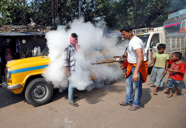 A taxi driver covers his face as a municipal worker fumigates a market to prevent the spread of dengue fever and other mosquito-borne diseases in Kolkata, India, November 20, 2017. (Photo by Rupak De Chowdhuri/Reuters)