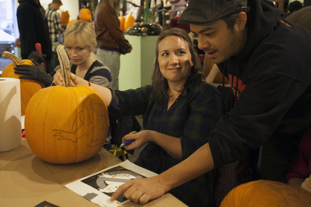 Chris Soria of the Maniac Pumpkin Carvers gives an attendee some tips on tackling a Ghostbuster design on a pumpkin at Cotton Candy Machine in Brooklyn, N.Y. on October 18, 2014. (Photo by Siemond Chan/Yahoo Finance)