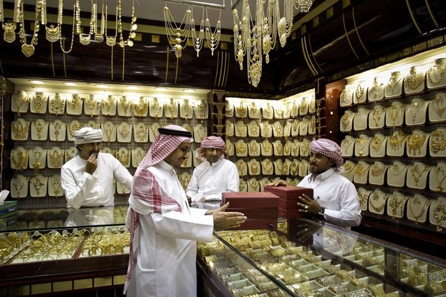 A Saudi customer discusses his purchases at a jewelry shop in the gold suq, or market, in Dubai, United Arab Emirates. The price of gold in Dubai is fixed daily and items are sold by weight. with little or no or little charge for the often exquisite workmanship. (Photo by Kamran Jebreili/AP Photo)