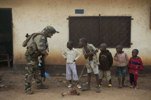 A French soldier talks to curious children as he mans a roadblock in the Miskine neighborhood of Bangui, Central African Republic, Monday, January 6, 2014. (Photo by Rebecca Blackwell/AP Photo)