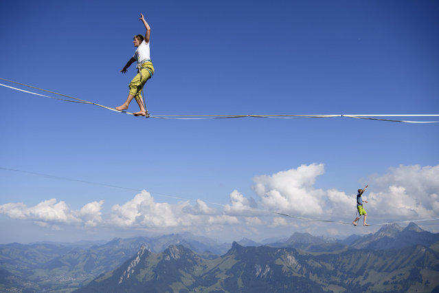 "Norwegean professional mountaineer Audhild Hogasen (L) and Dutch Yuri Rhodenborgh (R) walk on parallel lines during the Highline Extreme event on the top of the Moleson peak at 2000 meters above the sea level, in the Swiss Alps, near Fribourg, Switzerland, 08 September 2016. Twenty-five of the European best slackliners compete until 11 September, on eight different lines ranging from 45 metres to 495 metres. Balancing on the ""slackline"" is a training method for climbers to improve their equilibrium sense. To avoid the danger of falling down, the athletes are secured with a rope. (Photo by Laurent Gillieron/EPA)"