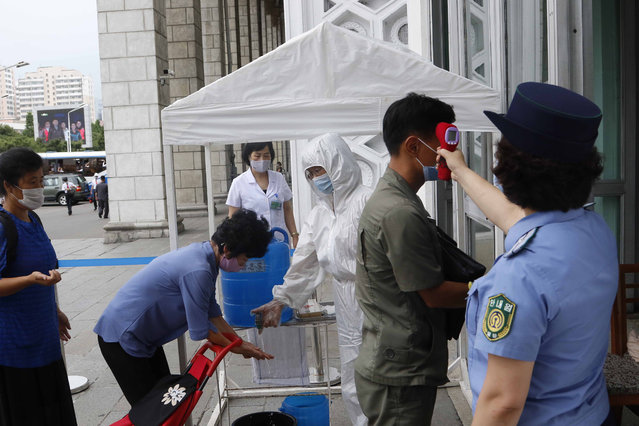 People are disinfected their hands and get fever checked before going into the Pyongyang Railway Station in Pyongyang, North Korea, Thursday, August 13, 2020. (Photo by Jon Chol Jin/AP Photo)