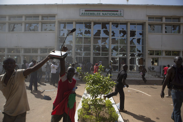 Anti-government protesters loot the parliament building in Ouagadougou, capital of Burkina Faso, October 30, 2014. (Photo by Joe Penney/Reuters)