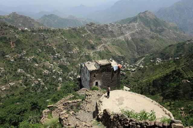 A boy stands on the roof of a pond in the mountains, in the Jafariya district of the western province of Raymah, Yemen June 2, 2016. (Photo by Abduljabbar Zeyad/Reuters)