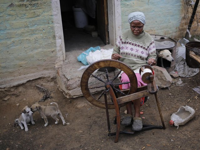 A women weaves cotton in the township in Nieu-Bethesda, South Africa, 10 November 2014. The tiny Karoo town has 2,000 people living in the township and only 60 in the village. The town is segregated along racial lines dating back to the apartheid area. Apartheid end in 1994 with the countries first free and fair elections. (Photo by Kim Ludbrook/EPA)