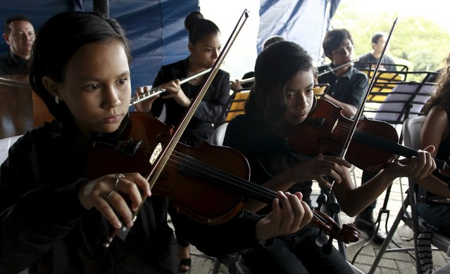 An orchestra comprised of the youths of the poor neighborhood of La Carpio perform during an inauguration ceremony of a water treatment by Costa Rica's President Luis Guillermo Solis in San Jose, Costa Rica September 10, 2015. (Photo by Juan Carlos Ulate/Reuters)