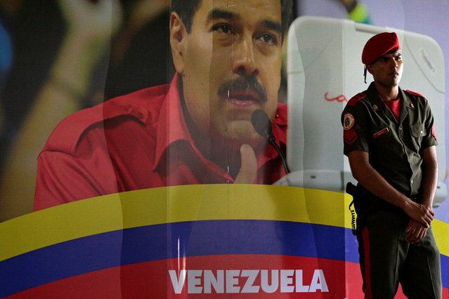 A soldier stands guard next to a portrait of Venezuela's President Nicolas Maduro at the International Press Center of the 17th Non-Aligned Summit in Porlamar, Venezuela September 15, 2016. (Photo by Marco Bello/Reuters)